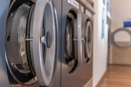 Detail of an industrial washing machine in the foreground, inside a laundry with a bokeh effect Stok Fotoğraf - 159101788