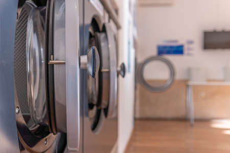 Detail of an industrial washing machine in the foreground, inside a laundry with a bokeh effect Stok Fotoğraf - 159101817