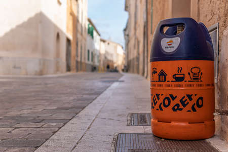 Campos, Balearic Islands / Spain; November 2020: an empty butane cylinder at the door of a house waiting for the butane delivery truck