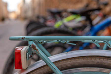 Detail of an old green bicycle, parked in the street with the background out of focus Stok Fotoğraf - 159051289