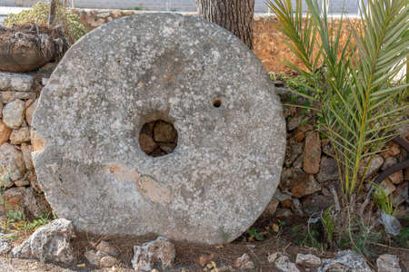 Traditional millstone resting on a rustic stone wall. Island of Mallorca, Spain Stok Fotoğraf - 159068610