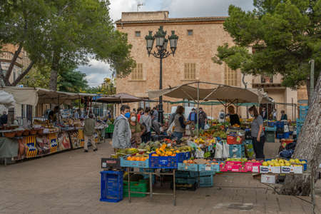 Campos, Balearic Islands / Spain; November 2020: fruit and vegetable stall at the traditional street market in Campos. Seller and buyers with facial masks for the new social measures by the Covid-19