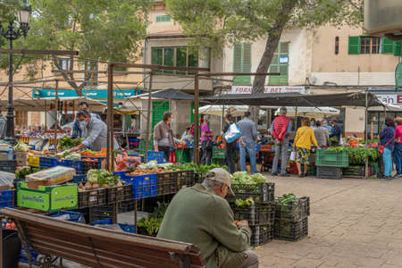 Campos, Balearic Islands / Spain; November 2020: fruit and vegetable stall at the traditional street market in Campos. Seller and buyers with facial masks for the new social measures by the Covid-19 Stok Fotoğraf - 159202324