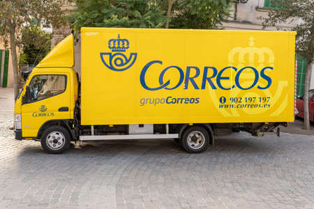 Porreres, Balearic Islands / Spain; November 17 2020: yellow mail delivery truck parked on a public street. Public postal service in Spain Stok Fotoğraf - 159204628