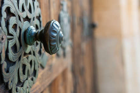 Detail of an antique door handle made of bronze with the background out of focus for the copy-space