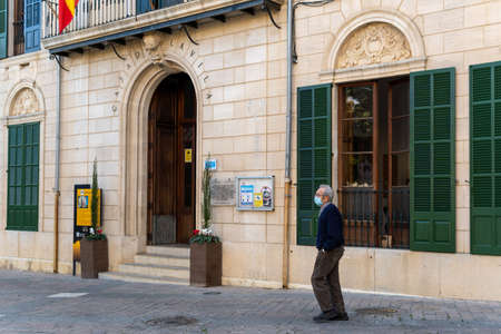 Porreres, Balearic Islands / Spain; November 17 2020: facade of the town hall of the town of Porreres, island of Mallorca. An old man with a face mask walking down te street Stok Fotoğraf - 159277023