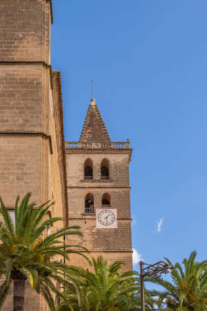 Church bell tower in the Majorcan town of Porreres on a sunny day surrounded by palm leaves