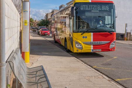 Campos, Balearic Islands / Spain; November 2020: bus of line of the island of Majorca that unites the towns with the capital. Bus stop in the town of Campos. Driver with face mask Stok Fotoğraf - 159559225