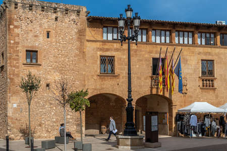Campos, Balearic Islands / Spain; November 2020: weekly street market of clothing and apparel in the town hall square in Campos. Social distance measuraments and face mask. New normal