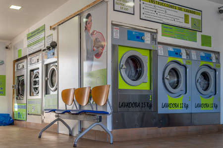 Campos, Balearic Islands / Spain; November 23 2020: interior of an industrial laundry without customers on a sunny day Stok Fotoğraf - 159562175