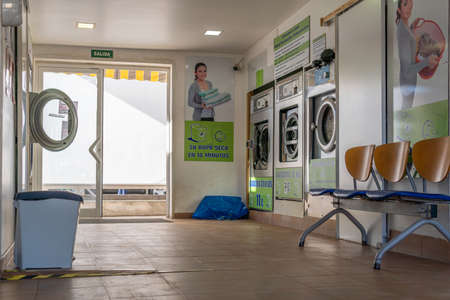 Campos, Balearic Islands / Spain; November 23 2020: interior of an industrial laundry without customers on a sunny day