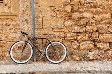Campos, Spain; november 2020: brown bicycle tied with a chain to a metal post in a village street with a background of a rustic stone facades