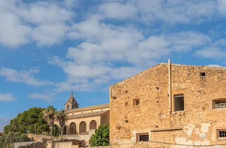 Church in the Majorcan town of Campos next to a rustic stone building. Majorca island, Spain Stok Fotoğraf - 159675643