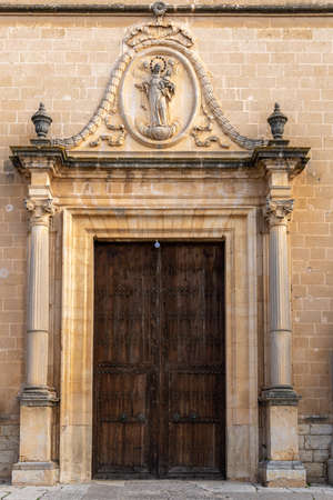 Main door of the church in the town of Porreres. Large wooden door with a stone sculptured relief of the Virgin Mary with the Child Jesus and the angels