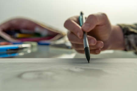Close-up of a hand drawing with a pencil, with the foreground and the background are out of focus Stok Fotoğraf