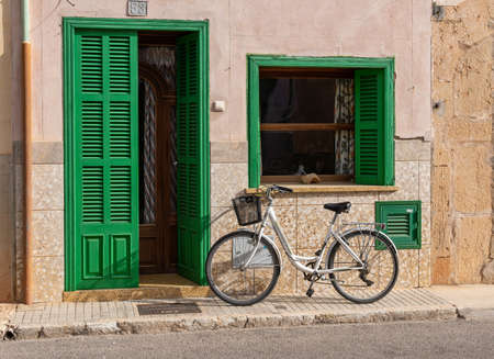 Campos, Spain; november 2020: white bicycle parked in front of a typical Majorcan country house with green shutters Stok Fotoğraf - 159832552