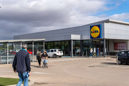 Campos, Spain; December 2020: entrance of a supermarket of a German food chain. At the entrance customers leave with food trolleys and face mask. New normal
