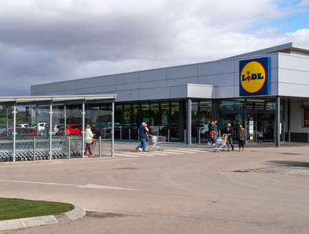 Campos, Spain; December 2020: entrance of a supermarket of a German food chain. At the entrance customers leave with food trolleys and face mask. New normal Stok Fotoğraf - 160350124