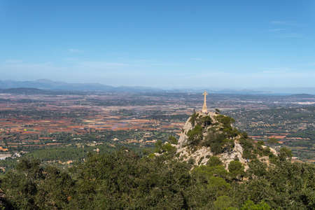 General view of the island of Mallorca from the Sanctuary of Sant Salvador. Image of the great cross sculpted in stone Stok Fotoğraf
