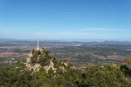 General view of the island of Mallorca from the Sanctuary of Sant Salvador. Image of the great cross sculpted in stone Stok Fotoğraf - 160672155