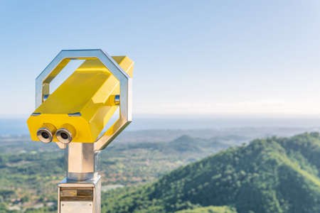Yellow metallic binoculars, with a blurred background of a Mediterranean landscape on a sunny day