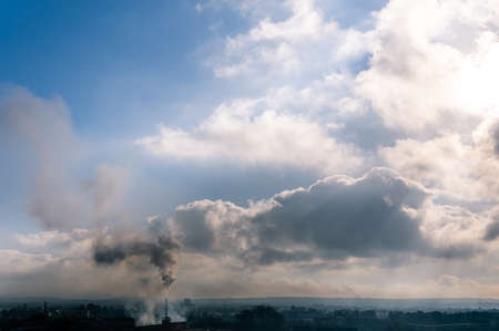 Chimney of a ceramic industrial oven drawing a black smoke towards a blue sky with cloudy intervals. Image of the climate change Stok Fotoğraf - 160758872