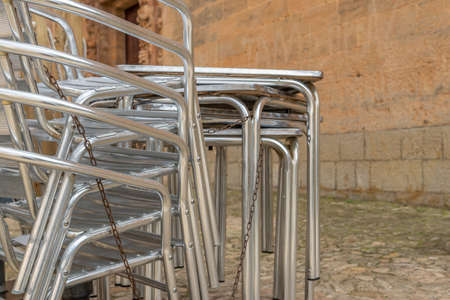 Metal chairs and tables stacked outdoor. Restaurant businesses closed by Coronavirus crisis Stok Fotoğraf