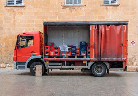 Llucmajor, Spain; December 17 2020: red beverage delivery truck parked. Inside the truck, boxes of soft drinks to be distributed to restaurants Stok Fotoğraf - 161123372