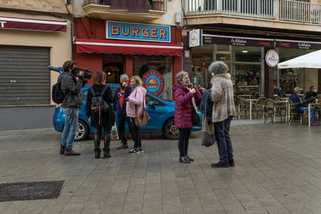 Llucmajor, Spain; December 17 2020: interview of people on the street by journalists all wearing face masks because of the Coronavirus pandemic Editöryel