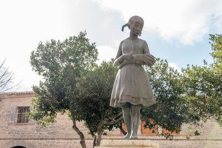 Llucmajor, Spain; December 17 2020: public bronze sculpture called Espigolera representing a girl with spikes in her hands Stok Fotoğraf - 161123608