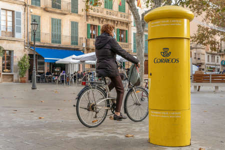 Llucmajor, Spain; December 17 2020: yellow mailbox of the Spanish postal service. In the background the image of a square with a woman riding a bicycle with a face mask because of the Coronavirus