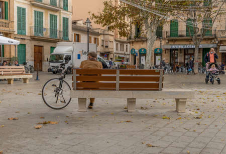 Llucmajor, Spain: december 17 2020: older person sitting on a public bench with a face mask on his bike in the main square of Llucmajor. New normal