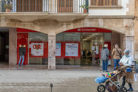 Llucmajor, Spain; December 17 2020: facade of a Spanish bank with clients wearing a face mask, waiting outside due to the measures taken by Coronavirus. -new normal