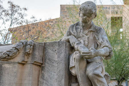 Llucmajor, Spain; December 17 2020: sculpture in homage to the shoemaker's guild, made in stone in a public square, in the town of Llucmajor Stok Fotoğraf - 161124252