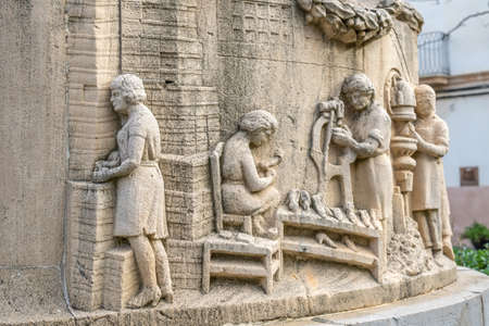 Llucmajor, Spain; December 17 2020: close-up of the sculpture in homage to the shoemaker's guild, made in stone in a public square, in the town of Llucmajor
