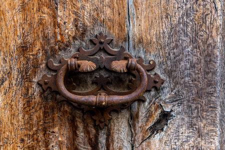 Close-up of an antique iron knob on an antique wooden door. Mallorca island, Spain