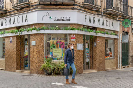 Llucmajor, Spain; decemeber 17 2020: front of a pharmacy with a person walking down the street wearing a face mask. New normal Editöryel