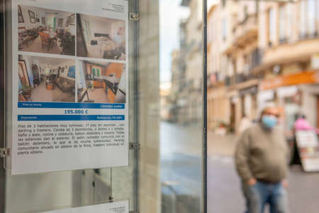 Llucmajor, Spain; December 17 2020: showcase of a real state agency. In the unfocused background a man walking down the street. New normality concept Editöryel