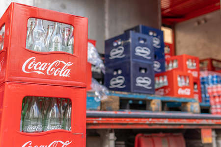 Llucmajor, Spain; December 17 2020: close-up of a red box of the Coca Cola brand, with empty glass bottles of Coca Cola