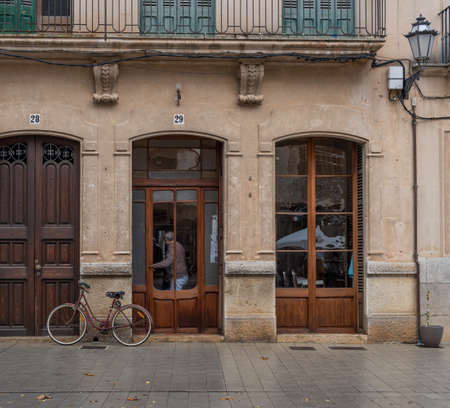 Llucmajor, Spain; December 17 2020: entrance of a vintage hairdresser's with a bicycle parked in front it, and a client leaving the premises wearing a face mask. New normal Editöryel