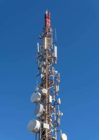 Cell phone and TV repeater with a blue sky background