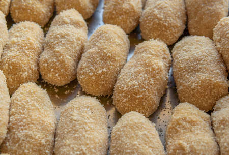 Close-up of homemade chicken croquettes prepared in a metal tray before frying in oil