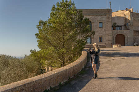 Blonde girl with face mask taking pictures with a camera to a Mediterranean landscape on the island of Mallorca, Spain. New normal