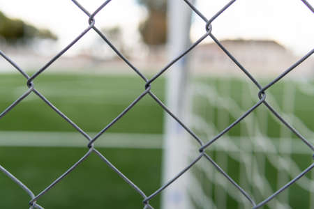 Empty soccer field closed with a metal fence. Covid-19 crisis. New normal concept