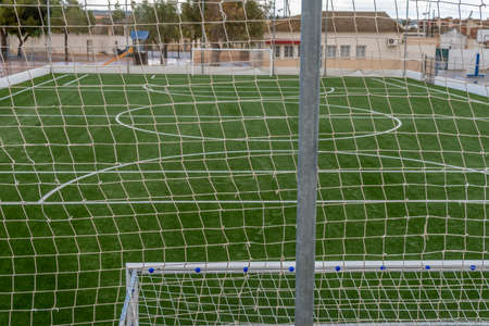 Empty soccer field closed with a metal fence. Covid-19 crisis. New normal concept Stok Fotoğraf - 161628834