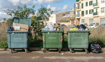 Campos, Spain; January 03 2020: three green trash containers filled with trash bags