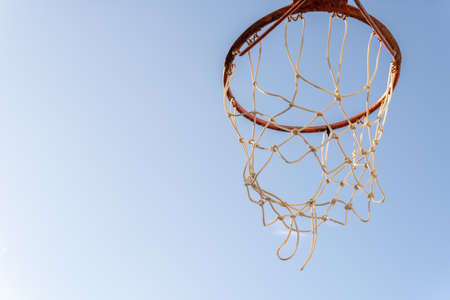 Close-up of a basketball hoop with a blue sky background