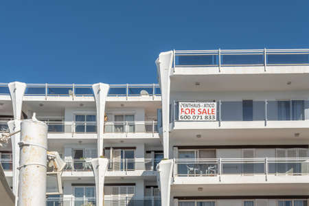 Palmanova, Spain; February 20 2021: facade of a tourist apartment building empty of tourists and with a for sale sign. Tourist crisis due to Coronavirus mobility restrictions