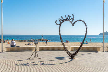 Palmanova, Spain; February 20 2021: maritime promenade of the Majorcan tourist locality of Palmanova, with an iron heart sculpture. People wearing a face mask. New normal concept