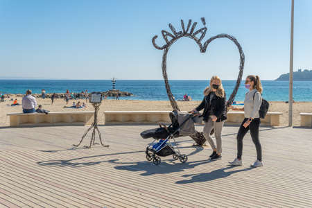 Palmanova, Spain; February 20 2021: maritime promenade of the Majorcan tourist locality of Palmanova, with an iron heart sculpture. Pedestrians walking with a face mask. New normal concept